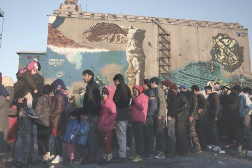 Μετανάστες και πρόσφυγες στέκονται στην ουρά για να παραλάβουν φρούτα και τσάι από ομάδα εθελοντών μετά την άφιξή τους στο λιμάνι του Πειραιά, την Πέμπτη 25 Φεβρουαρίου 2016. Πάνω από 2000 πρόσφυγες και μετανάστες έφτασαν μέχρι το μεσημέρι στο λιμάνι του Πειραιά προερχόμενοι από τα νησιά. Οι μετανάστες κατευθύνθηκαν στους επιβατικούς σταθμούς του λιμανιού του Πειραιά όπου φιλοξενούνται προσωρινά ενώ κάποιοι από αυτούς αναμένεται να οδηγηθούν στα κέντρα προσωρινής κράτησης με πούλμαν.